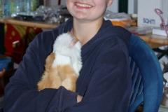 eine strahlende Tomke mit ihrem Lieblingsschweinchen auf dem Arm